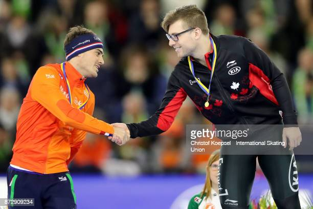 Jan Smeekens of the Netherlands won the second oplace and congratulates winner Laurent Dubreuil of Canada on the podium after the men 500m Division A...