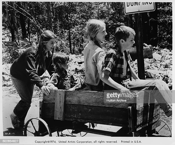 Jan Smithers pushes Matthew Burrill Helen Harmon and Julie Gholson in a wagon in a scene for the United Artist movie Where the Lilies Bloom circa 1974