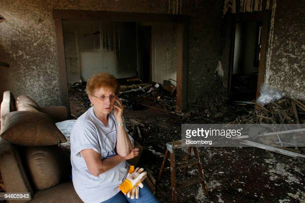 Jan Sommerfeld talks on the phone as she takes a break from salvaging items from her brother inlaw's destroyed home in Greensburg Kansas Tuesday May...