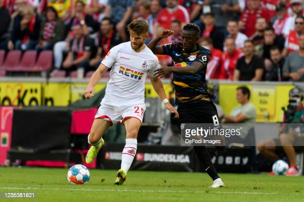 Jan Thielmann of 1. FC Koeln and Amadou Haidara of RB Leipzig battle for the ball during the Bundesliga match between 1. FC Koeln and RB Leipzig at...