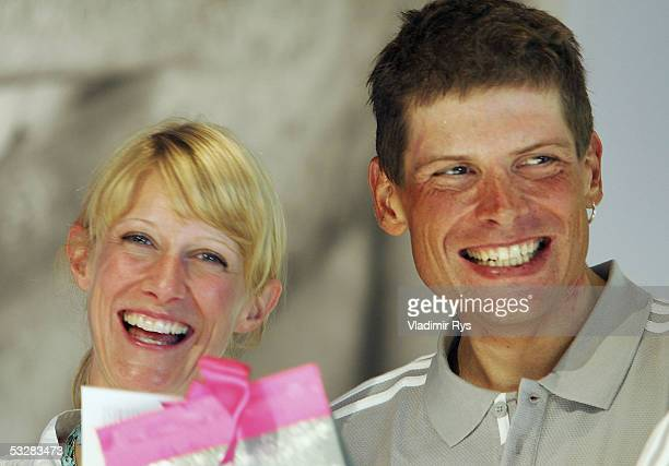 Jan Ullrich of Germany smiles with his girlfriend Sara Steinhauser during the arrival of the TMobile cycling team after the completion of the Tour de...