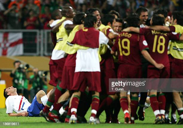 Jan Vennegoor of Hesselink lies on the ground as Portugal celebrate victory at the end of the game. Despite playing two men short Portugal hung on to...