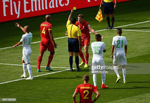 Jan Vertonghen of Belgium is shown a yellow card by referee Marco Rodriquez after a foul on Sofiane Feghouli of Algeria resulting in a penalty kick...