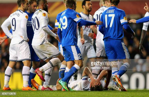 Jan Vertonghen of Tottenham Hotspur lies on the pitch after an altercation with Roman Zozulya of FC Dnipro who is subsequently shown a red card and...