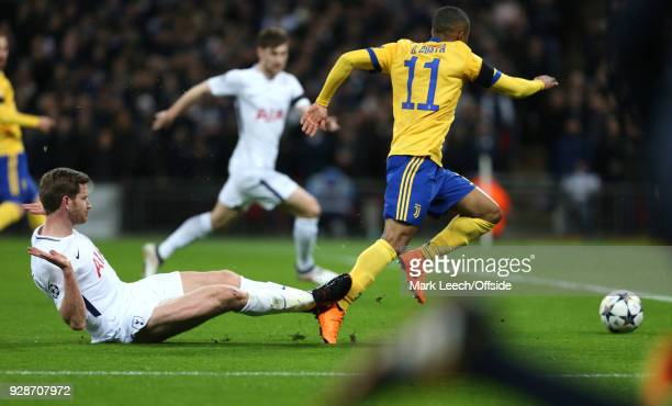 Jan Vertonghen of Tottenham slide tackles Douglas Costa of Juventus in the box but a penalty is not given for the challenge during the UEFA Champions...