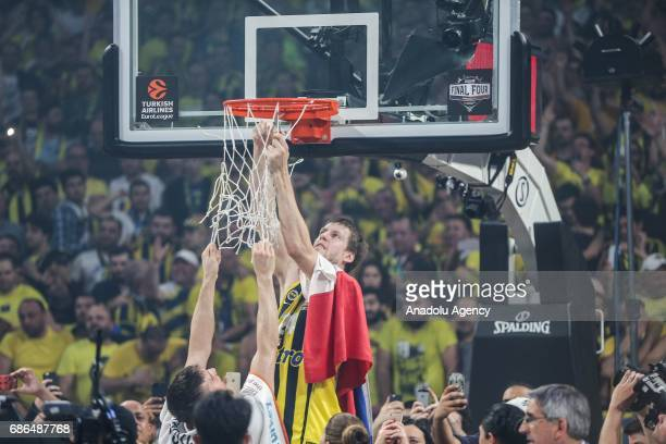 Jan Vesely of Fenerbahce cuts the net as they celebrate their victory after receiving the cup in Turkish Airlines Euroleague Final Four championship...