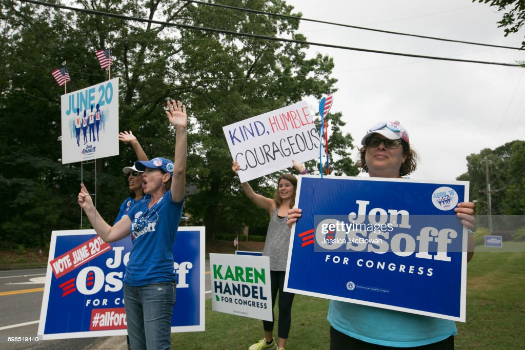 Jan Yanes (left) and Tammy Harper of Roswell, supporters of Democratic candidate Jon Ossoff, wave at cars passing by St. Mary's Orthodox Church of Atlanta on June 20, 2017 in Roswell, Georgia. Voters head to the polls to cast their vote in Georgia's 6th Congressional District special election. Republican Karen Handel and Democrat Jon Ossoff are running against each other in a special election to fill the congressional seat vacated by Secretary of Health and Human Services Tom Price.