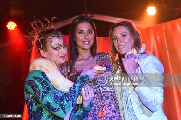 Jana Azizi and Simone Ballack with a snake charmer during 'Temple of Sun' the P1 summer party at P1 on July 17 2018 in Munich Germany