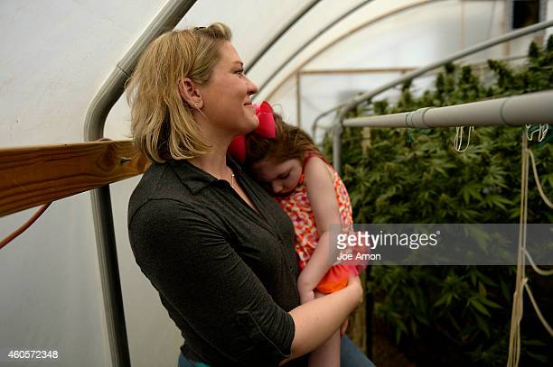 August 05: Janéa Cox, director of the Flowering H.O.P.E. Foundation holds her daughter Haleigh as she looks at the marijuana plants she believes has...