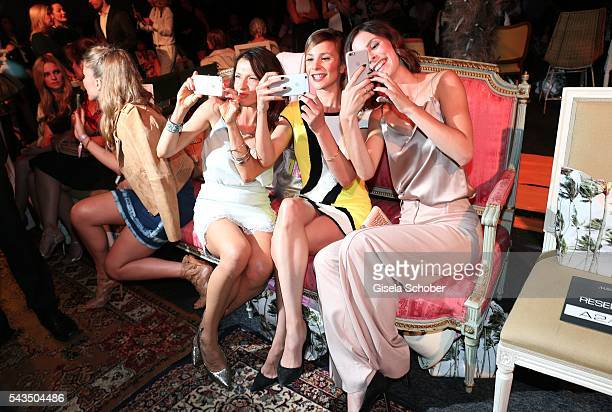 Jana Pallaske Aylin Tezel and Lena MeyerLandrut photograph with their mobile phones during the Marc Cain fashion show spring/summer 2017 at CITY CUBE...