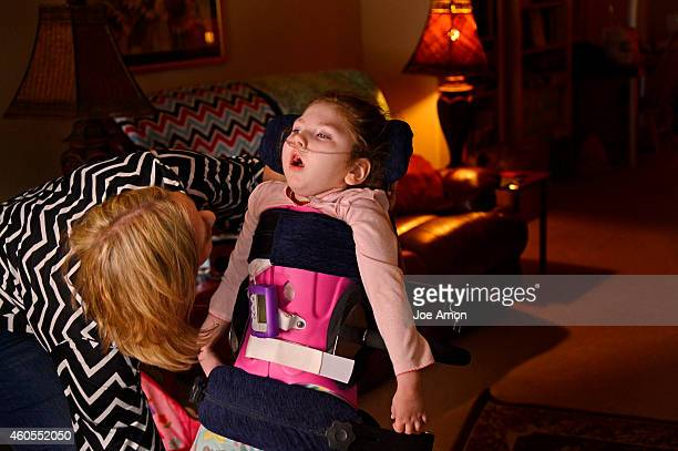October 03: Janéa Peloquin Cox tightens the straps of a special machine that lets her 5-year-old daughter stand. Janéa lives here with Haleigh, who...
