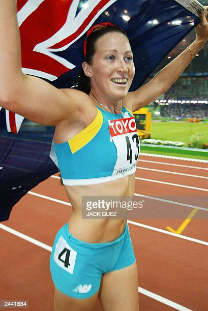 Jana Pittman of Australia carries her national flag after she won the women's 400m hurdles final 28 August 2003 during the 9th Athletics World...