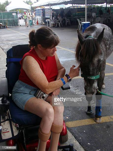 Jana Thomas of Pembroke Pines pets Molly the pony who has a prosthetic right front leg at the No Barriers Festival in Coconut Grove Florida
