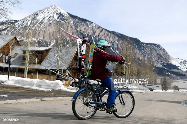 Janae Pritchett rides her bike with skis after a day on the mountain as Crested Butte experienced warm temperatures on Sunday March 11 2018