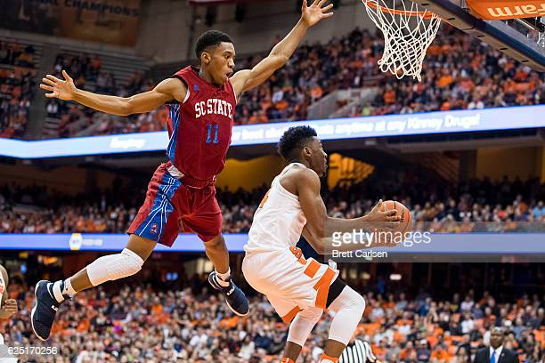 Janai Raynor Powell of the South Carolina State Bulldogs flies over a shooting John Gillon of the Syracuse Orange during the first half on November...