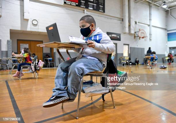 Jandel Diaz does his school work on a laptop computer. At the Mulberry Street location of the Olivet Boys and Girls Club in Reading Tuesday morning...