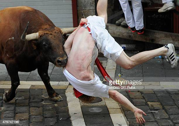 A Jandilla bull charges at a participant during the first 'encierro' of the San Fermin Festival in Pamplona northern Spain on July 7 2015 The...