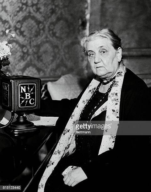 Jane Addams internationally known social worker and author seated before a NBC radio microphone Miss Addams established the social settlement Hull...