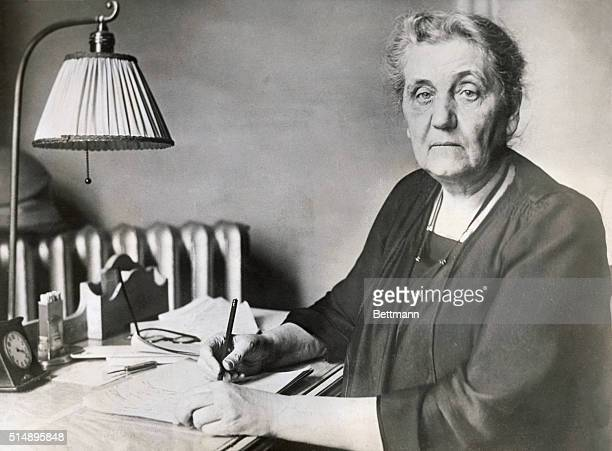 Jane Addams internationally known social worker and author writes at her desk Miss Addams established the social settlement Hull House in Chicago in...