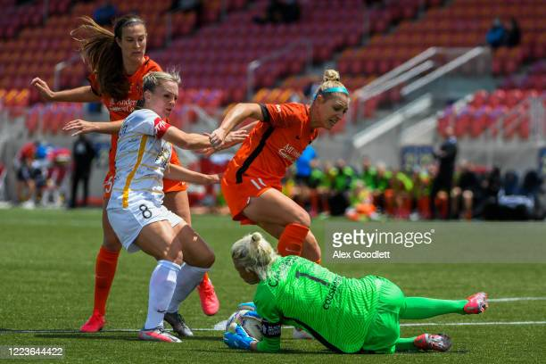 Jane Campbell of Houston Dash dives under Amy Rodriguez of Utah Royals FC for a stop during a game in the first round of the NWSL Challenge Cup at...