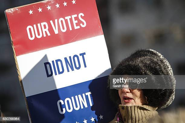 Jane Dailey of Lansing protests Presidentelect Donald Trump at a rally at the Michigan State Capitol before the state electoral college met to cast...