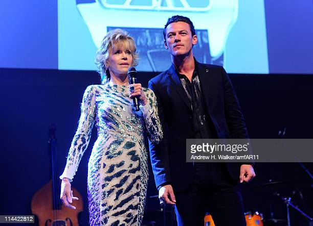 Jane Fonda and Luke Evans speak onstage at amfAR's Cinema Against AIDS Gala during the 64th Annual Cannes Film Festival at Hotel Du Cap on May 19...