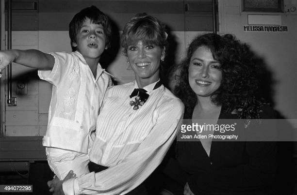 Jane Fonda holding her son Troy and singersongwriter Melissa Manchester backstage during a tribute to Muhammad Ali celebration at the Forum on...