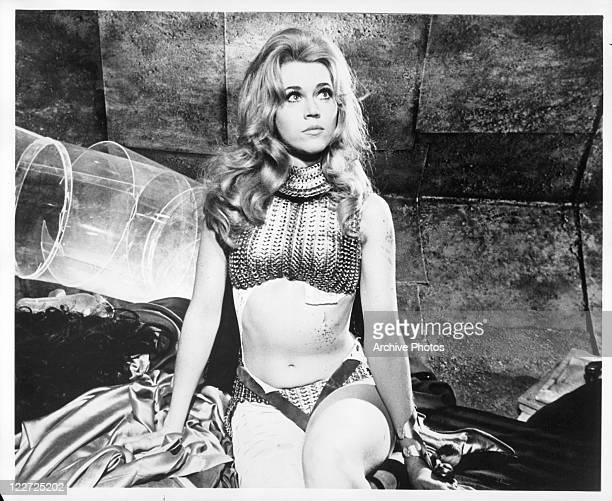Jane Fonda sitting in a scene from the film 'Barbarella' 1968