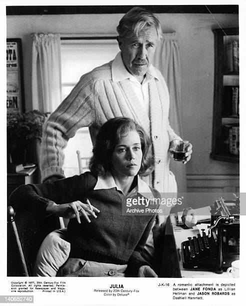 Jane Fonda sitting with Jason Robards standing beside her in a scene from the film 'Julia' 1977