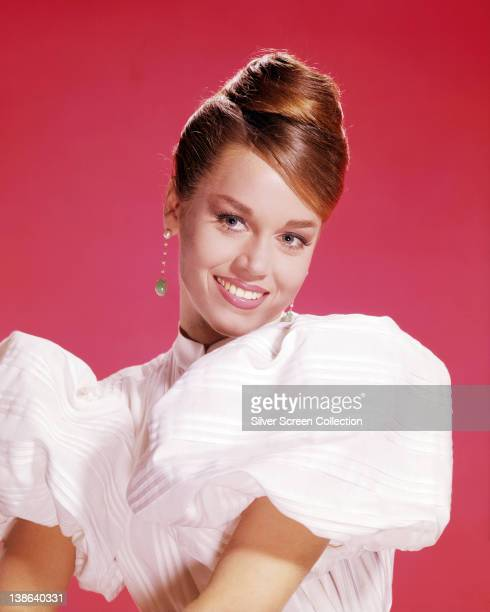 Jane Fonda US actress wearing a pink puff sleeve blouse and drop earrings in a studio portrait against a red background circa 1965