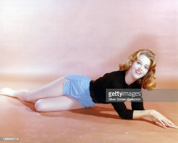Jane Fonda US actress wearing light blue shorts and a black top laying on the ground in a studio portrait circa 1960