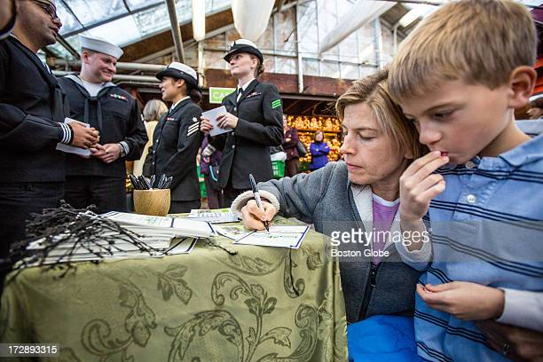 Jane Johnson left of Belmont and her son William sign a card after donating a tree to Trees for Troops at Mahoney's Garden Center in Winchester...