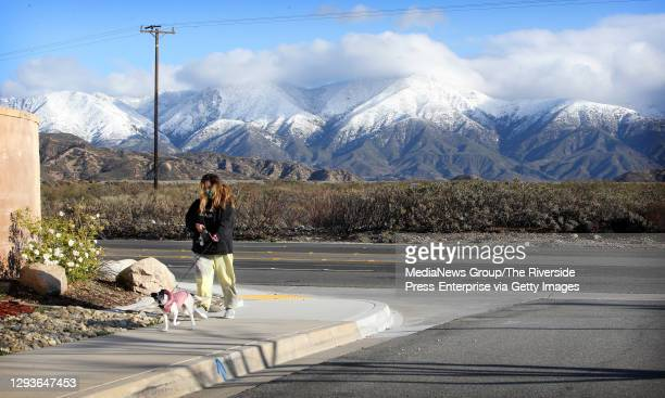 Jane Kim walks her dog Cooper against the backdrop of the snow-capped San Bernardino Mountains on Tuesday morning, Dec. 29 in the Las Colinas...