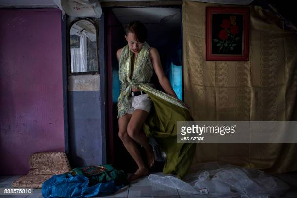 Jane Laut a transgender resident of Marawi tries on a curtain to serve as a gown inside the house of her friend on October 20 2017 in Saguiaran...