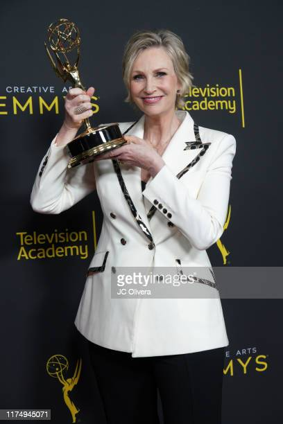 "Jane Lynch poses in the press room with the award for outstanding guest actress in a comedy series for ""The Marvelous Mrs. Maisel"" during the 2019..."