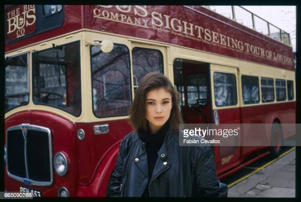 Jane March stands in front of a bright red doubledecker sightseeing bus The British actress plays the role of the young girl in French director...