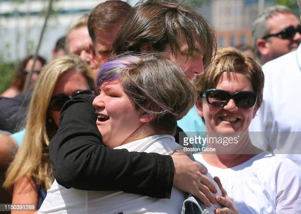 Jane Martin gets a hug from her brother Henry after she sang a song as her mother Denise looks on during the opening of Martin's Park in Boston on...