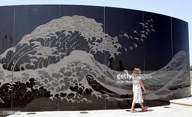 Jane Michele Becker from Chicago Illinois rubs her hand along the memorial of TWA Flight 800 at Smith Point Park 17 July 2006 in Shirley New York on...