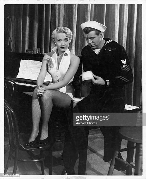 Jane Powell sitting at the piano with sailor Gene Nelson in a scene from the film 'Three Sailors And A Girl' 1953
