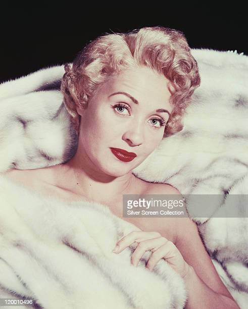 Jane Powell US actress dancer and singer reclining against a white fur surface covered up to her chest with white fur circa 1960