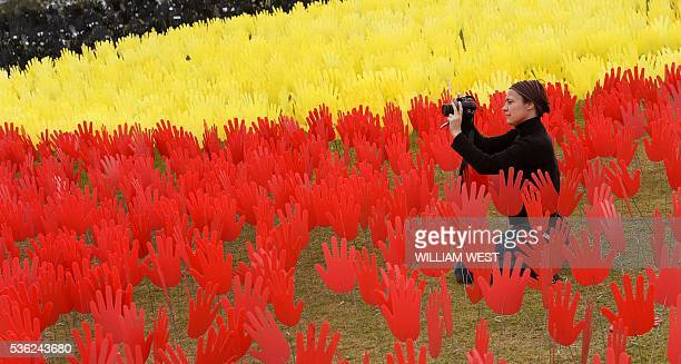 Jane Powles national campaign manager for ANTAR places hands in a huge art installation called 'Sea of Hands' which consists of thousands of hands in...