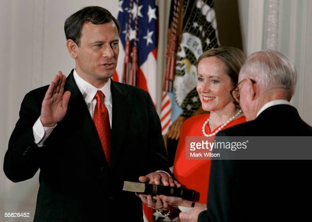 Jane Roberts holds a Bible as John Roberts raises his right hand as he is sworn in as Chief Justice of the United States Supreme Court by Associate...
