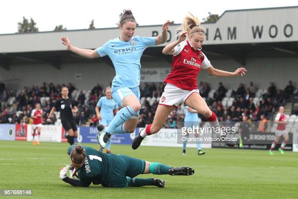 Jane Ross of Man City and Leah Williamson of Arsenal jump over Arsenal goalkeeper Sari Van Veenendaal as she comes out to make a save during the...