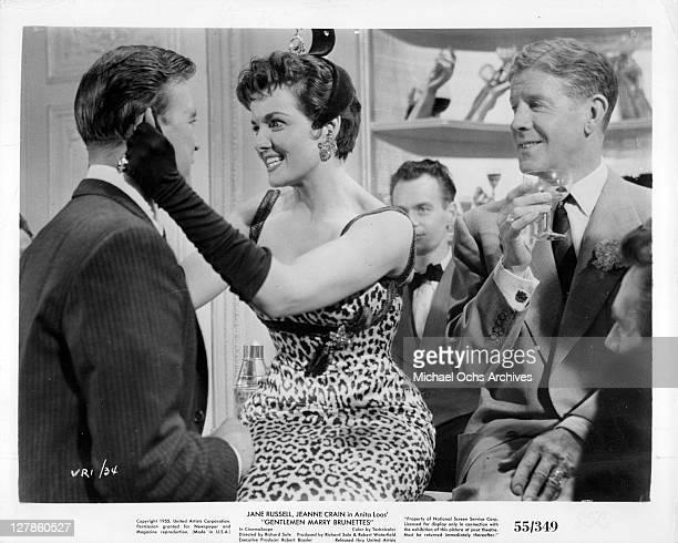 Jane Russell pulling on the ear of unidentified man in a scene from the film 'Gentlemen Marry Brunettes' 1955
