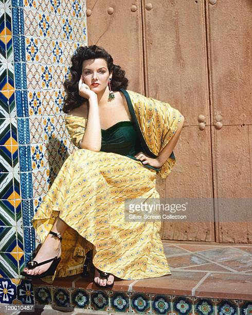Jane Russell US actress wearing a long yellow print patterned skirt with a matching shawl and a dark green top sitting with her head resting in her...