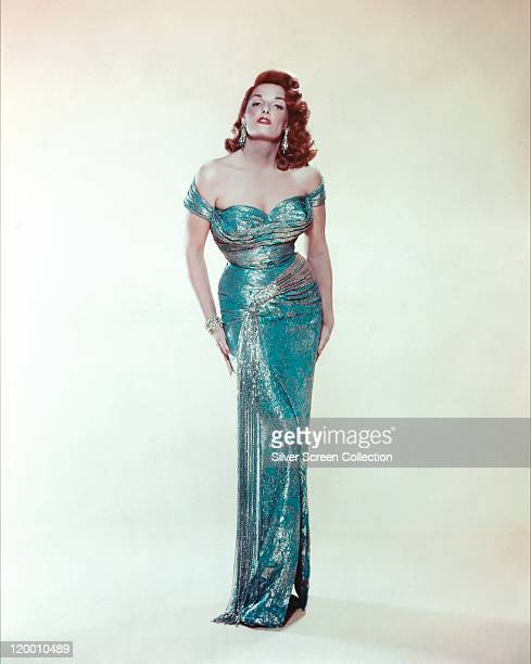 Jane Russell US actress with red hair wearing a long blue shoulderless dress in a studio portrait against a white background circa 1955