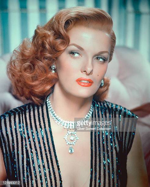 Jane Russell wearing a sleeveless black striped top with a plunging neckline and decorated with light blue sequins and an ornate diamond necklace...