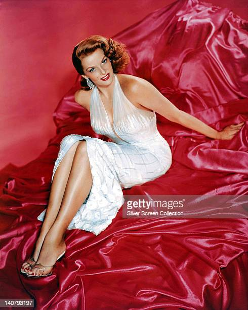 Jane Russell wearing a white halterneck dress and reclining on red silk sheets in a studio portrait against a red background circa 1945