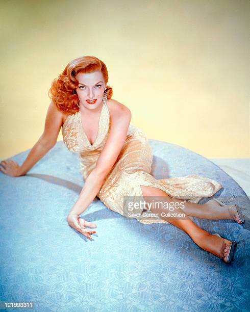 Jane Russell wearing a yellow dress while sitting on a large blue cushion in a studio portrait against a yellow background circa 1955