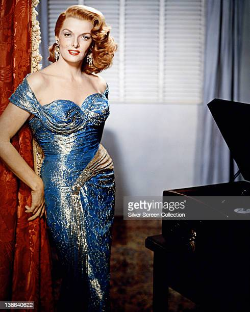 Jane Russell , wearing an off-the-shoulder blue and gold dress , with a red theatre curtain behind her, circa 1955.